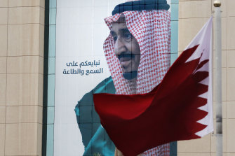 A Qatari flag flies in front of a banner portraying Saudi King Salman, in Riyadh, ahead of the Gulf states summit this week.