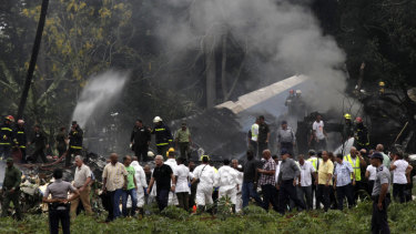 Cuban President Miguel Diaz-Canel, third from left, walks away from the site where a Boeing 737 plummeted into a yuca field with more than 100 passengers on board.