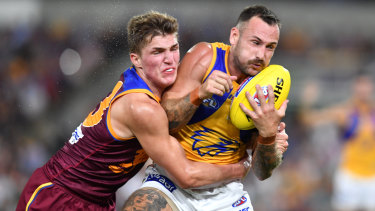 Fast and furious: West Coast's Chris Masten gets wrapped up by Zac Bailey of Brisbane.