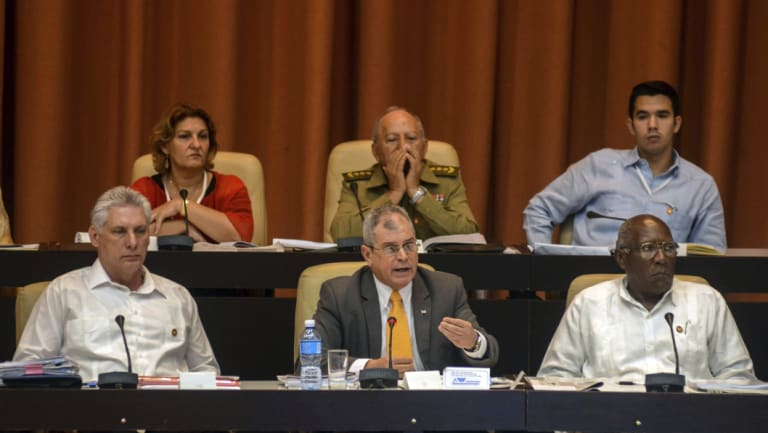 Cuban President Miguel Diaz-Canel, from left, Secretary, Council of State Homero Acosta Alvarez and First Vice President, Council of State Salvador Valdes Mesa, attend a National Assembly session in Havana, Cuba, on Saturday.
