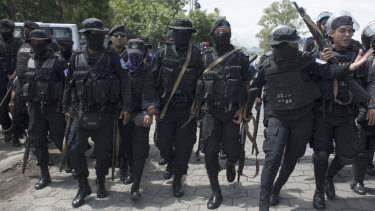 Armed police walk to break up an anti-government demonstration in Managua, Nicaragua.