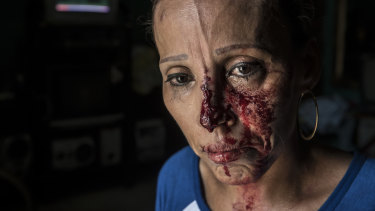 A woman with her face bloodied after she was pummeled by the police, stands in shock inside a house after a peaceful anti-government march was dissolved violently by government forces, in Managua, Nicaragua.