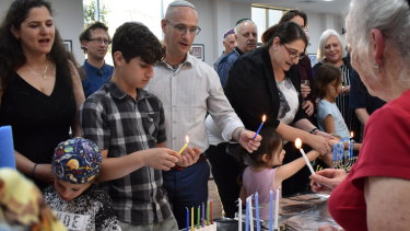 Rabbi Adi Cohen leads the chant as the Maces and other families light their prospective Chanukiahs on Shabbat day.