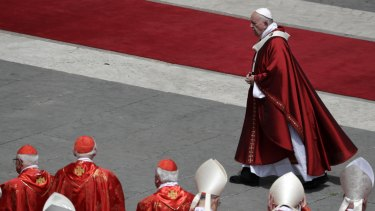 Pope Francis walks past cardinals after celebrating a Pentecost Mass in St Peter's Square at the Vatican.