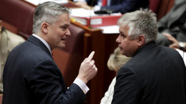 Minister for Finance Mathias Cormann in discussion with senator Rex Patrick in the Senate.