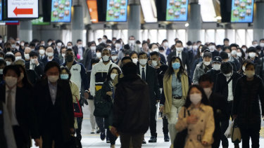 A station passageway is crowded with commuters wearing face mask during rush hour in Tokyo on Monday.