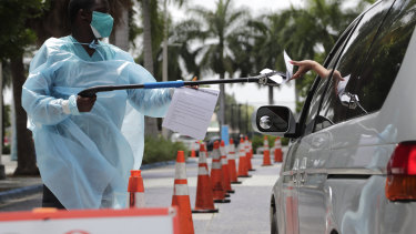 Healthcare worker Dante Hills, left, passes paperwork to a woman in a vehicle at a COVID-19 testing site in Miami.