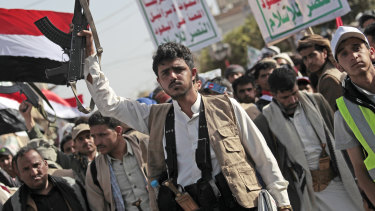 A Houthi supporter holds a weapon as he attends a rally marking six years for a Saudi-led coalition in Sanaa, Yemen.