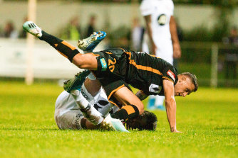 Kosta Grozos of the Wanderers and Jake Brimmer of the Glory clash during the FFA Cup at Dorrien Gardens in Perth on Wednesday night.