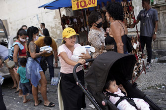 People collect food donated by aid groups in Rio de Janeiro, Brazil, on Wednesday.
