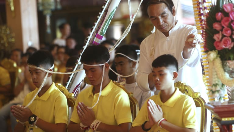 Ekaphol 'Ake' Chantawong, centre, and members of the rescued soccer team attend a Buddhist ceremony believed to extend the lives of its attendees as well as ridding them of dangers and misfortunes in Mae Sai, Chiang Rai province, northern Thailand, on Thursday.