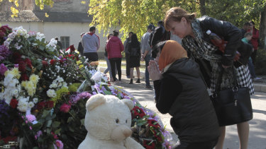 A woman prays near a memorial to the people killed during an attack in the vocational college in Kerch, Crimea.