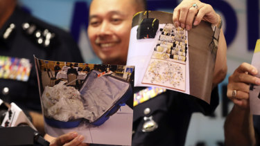 An officer of Malaysia's Federal Commercial Crime Investigation Department shows pictures of jewellery seized from Najib.