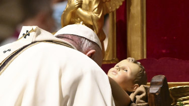 Pope Francis kisses a statue of Baby Jesus as he celebrates Mass on Christmas Eve, at St Peter's basilica at the Vatican.