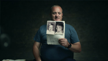 Jason King, the subject of <i>Ghosthunter</i>, holds a photo of himself from his childhood medical files.