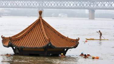 Residents swim past a riverside pavilion submerged by the flooded Yangtze River in Wuhan in central China's Hubei province.