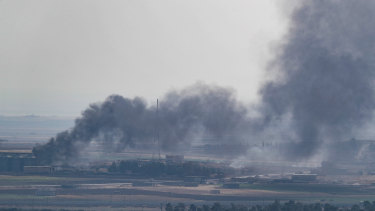 Smoke rises over the Syrian town of Ras al-Ain, as seen from the Turkish border town in Ceylanpinar, Turkey.