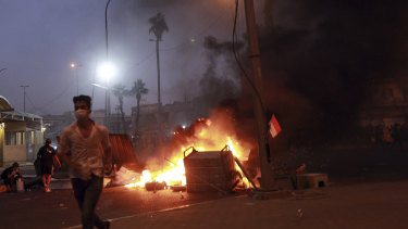 Protesters set fires while security forces take aim at them with guns and tear gas in Baghdad.