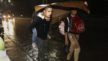 Migrants begin their journey towards the distant United States under a steady rain as a caravan of several hundred sets off walking from a main bus station in San Pedro Sula on Monday.