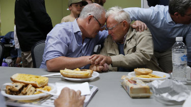Scott Morrison comforts 85-year-old Owen Whalan of Half Chain road during a visit to Club Taree Evacuation Centre in Taree.