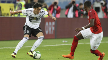 Germany's Mesut Ozil (left) vies for the ball with Austria's David Alaba.