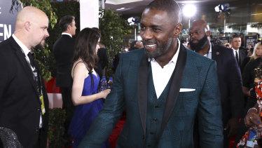 A dashing Idris Elba arrives at the Golden Globes.