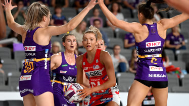 Swamped: Swifts attack Helen Housby surrounded by the Firebirds defence yesterday.