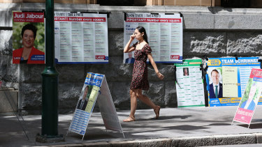 """A voter walks past """"how to vote"""" boards, in the absence of volunteers, in Brisbane."""