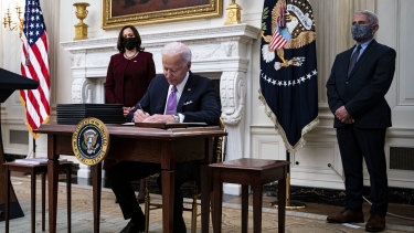 US President Joe Biden signs an executive order after speaking during an event on his administration's COVID response with Vice-President Kamala Harris, left, and Dr Anthony Fauci, director of the US National Institute of Allergy and Infectious Diseases.
