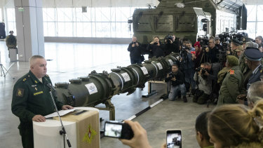 Lieutenant General Mikhail Matveevsky, the chief of the Russian military's missile and artillery forces, speaks during a briefing by the Russian Defence Ministry. A 9M729 land-based cruise missile is displayed near its launcher.