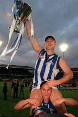 John Longmire, with the 1999 AFL premiershhip cup, sits on teammate Martin Pike's shoulders.