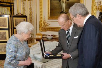 The Queen watches on as Australia's then high commissioner to the UK Alexander Downer presents the insignia to Prince Philip.