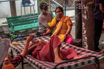 Patients suffering from COVID-19 are treated with free oxygen at a makeshift clinic in India.