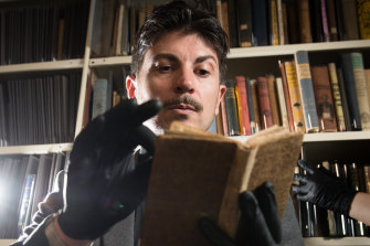 Adam Mada holding a rare book, The Whole Art of Legerdemain, or Hocus Pocus in Perfection, State Library of NSW containing magician's secrets to teach stagecraft to students at NIDA.