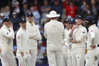 England's players watch the replay of a no-ball delivered to Steve Smith.