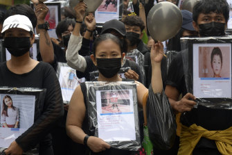 Anti-coup protesters holding pictures of those who died during a protest offer prayers for them.