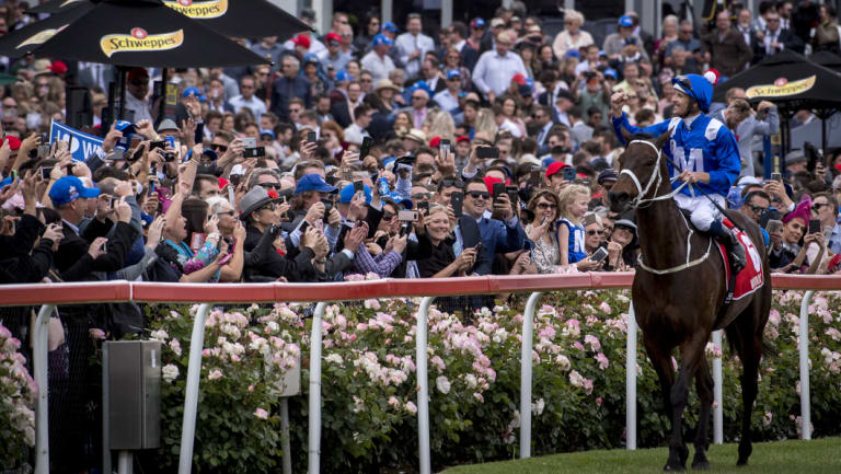 Winx and jockey Hugh Bowman salute the crowd after winning the Cox Plate for the fourth time.