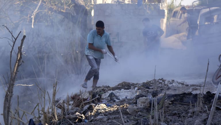 Syrians use dirt to put out a fire at the scene of a reported air strike in the district of Jisr al-Shughur, in the Idlib province, on September 4.
