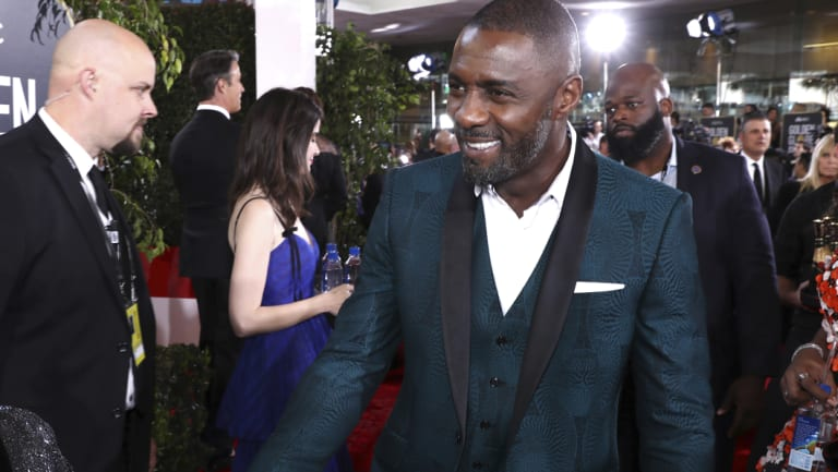 A dashing Idris Elba arrives at the Golden Globes.
