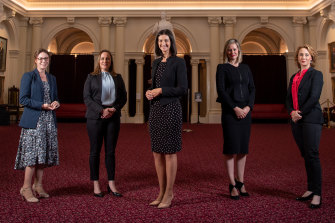 Ali Cupper, Bridget Vallence, Ellen Sandell, Steph Ryan and Gabrielle Williams in the Queen's Hall at Parliament, surrounded by portraits of Victoria's premiers, all but one of whom were male.