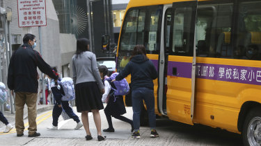 Children get off a school bus as most schools were reopened after being closed for several days in Hong Kong, Wednesday, Nov. 20, 2019. A small band of anti-government protesters, their numbers diminished by surrenders and failed escape attempts, remained holed up at a Hong Kong university early Wednesday as they braced for the endgame in a police siege of the campus. (AP Photo/Achmad Ibrahim)