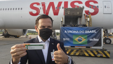 Sao Paulo Governor Joao Doria flashes a thumbs up next to a container carrying the experimental CoronaVac after it was unloaded from a cargo plane arriving from China on December 3.