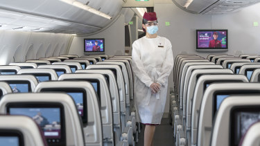 A flight attendant wearing protective equipment on board Qatar Airways. Akbar Al Baker, chief executive of the airline, says the pandemic will force a mindset shift similar to how 9/11 transformed aviation security procedures.
