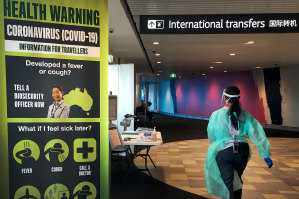 A staff member in protective medical clothing moves through the arrivals area at Brisbane International Airport.