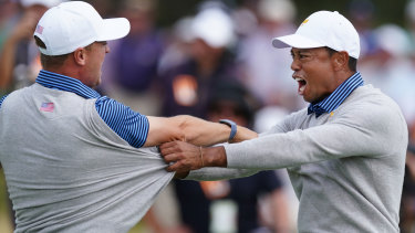 Back in it: Tiger Woods and Justin Thomas  celebrate their victory on Friday.