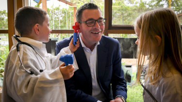 Premier Daniel Andrews gets a check-up from Mitchell and Isabelle at a kindergarten in Pakenham.