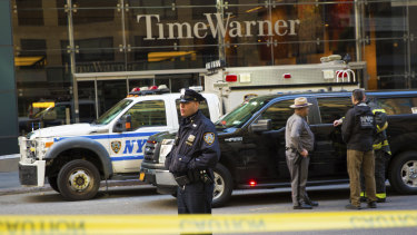 An officer keeps watch in front of the Time Warner Building, where NYPD personnel removed an explosive device on Wednesday in New York.
