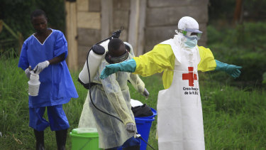 A health worker sprays disinfectant on his colleague after working at an Ebola treatment centre in Beni, Eastern Congo.