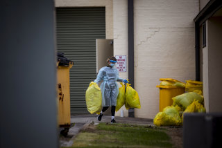 A worker disposes of hazardous waste during a deep clean at St Basil's on July 28.