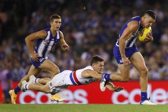 The Kangaroos' Luke Davies-Uniacke on the run as Josh Dunkley dives to tackle.